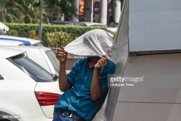 A boy covers his face with handkerchief to protect himself from the scorching sun on a hot summer day at Connaught Place on June 7 2018 in New Delhi...
