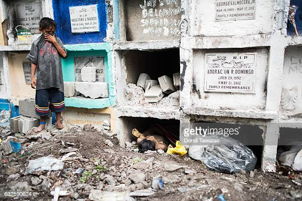 A boy covers his mouth while looking at bodies being buried on January 24 2017 in Manila Philippines Many bodies of victims of extrajudicial killings...