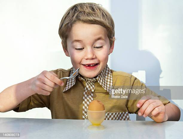 Boy cracking a boiled egg with a spoon