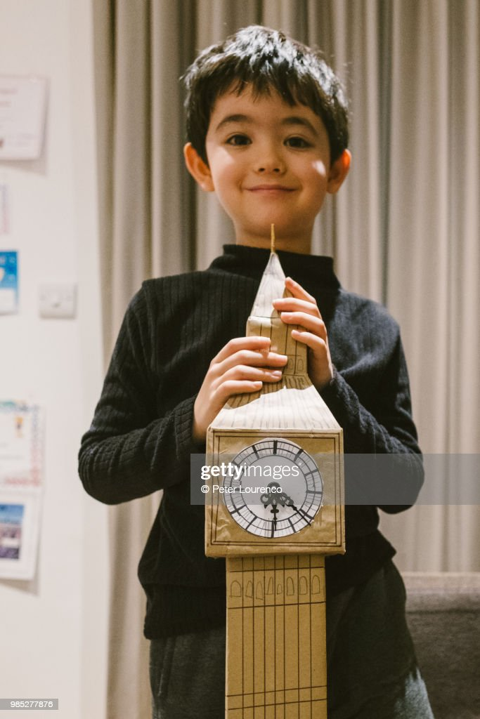 Boy crafting a clock tower out of cardboard : Photo