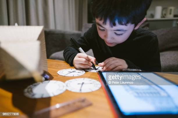 Boy crafting a clock tower out of cardboard