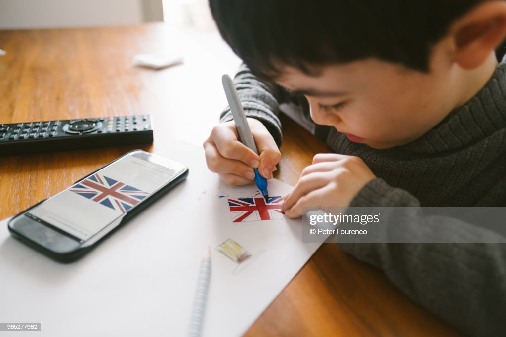 Boy crafting a clock tower out of cardboard : Stock Photo