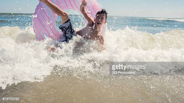 boy crashes on the waves in the ocean - galveston stock pictures, royalty-free photos & images