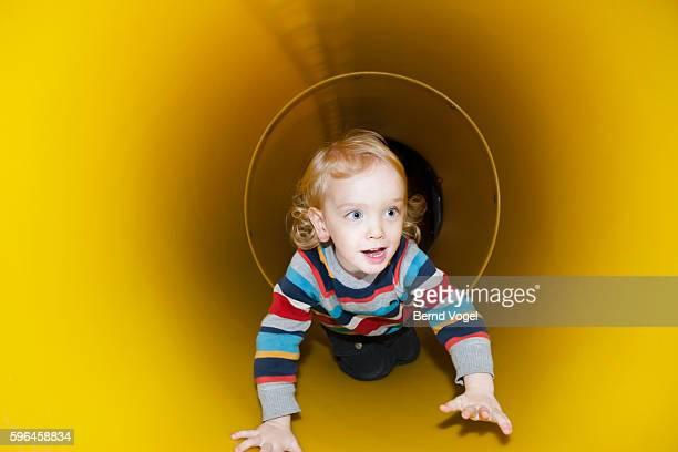 Boy crawling inside yellow tunnel