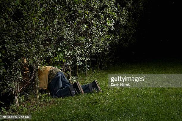 Boy (8-9) crawling into bushes in dark yard at night, side view, low section