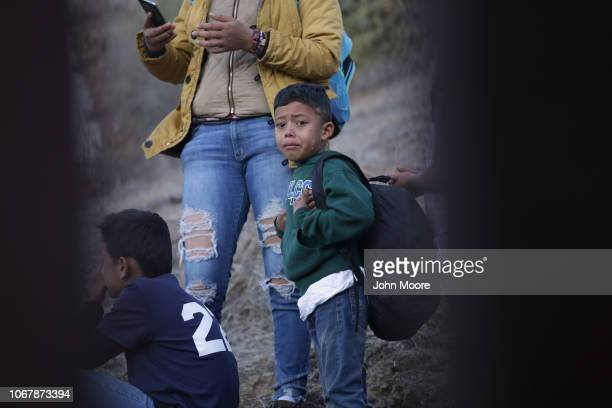 A boy cries after a chaotic crossing over the USMexico border fence on December 2 2018 from Tijuana Mexico Numerous members of the caravan were able...