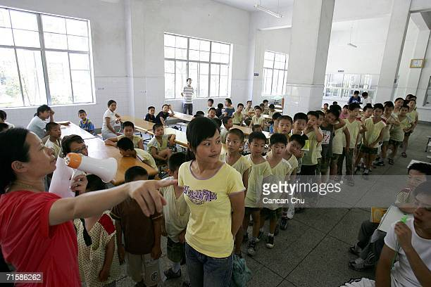 Boys line up to attend a meeting at the West Point Training Center ANGZHOU ZHEJIANG AUGUST 03 A boy cries after being in a fight with his classmate...