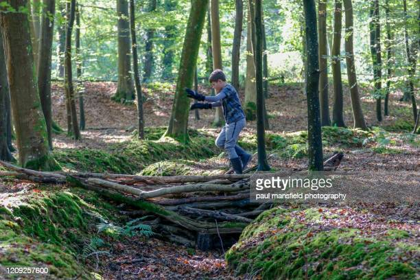 boy crossing makeshift bridge in woodland - makeshift stock pictures, royalty-free photos & images