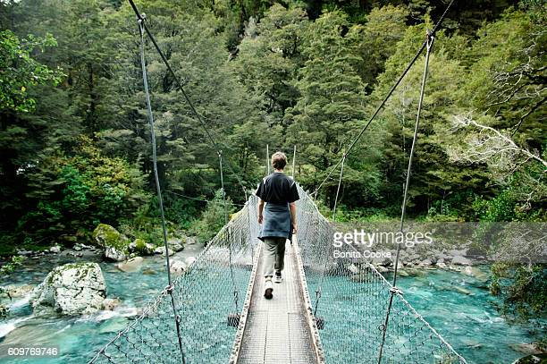 Boy crossing swing bridge over river in Hollyford Valley