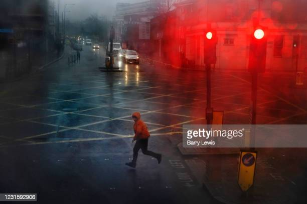 Boy crossing the road during a wet day in the Kings Cross area during the third lockdown of the Coronavirus pandemic, on 3rd March 2021, in London,...