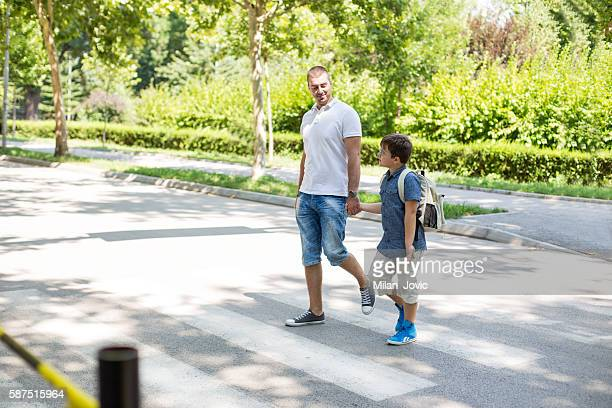 Boy crossing the street with his father