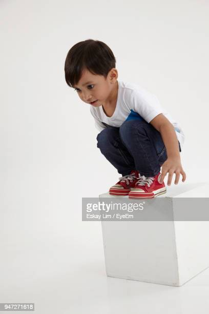 Boy Crouching On Block Shape Against White Background