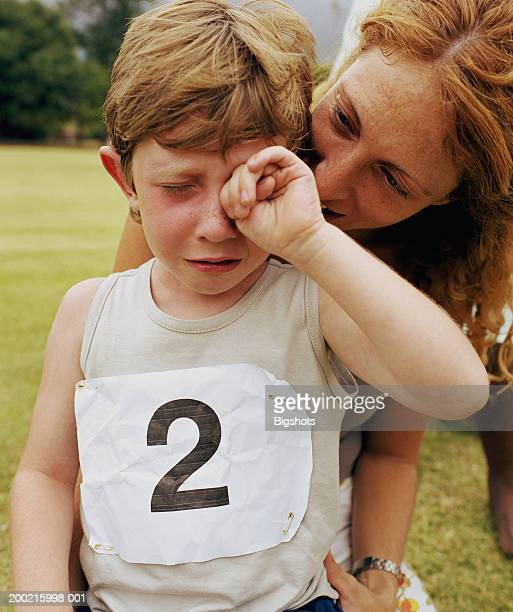 Boy (4-6) crying being comforted by mother, close-up