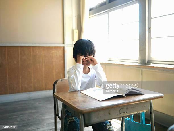 Boy (5-7) crying in school classroom