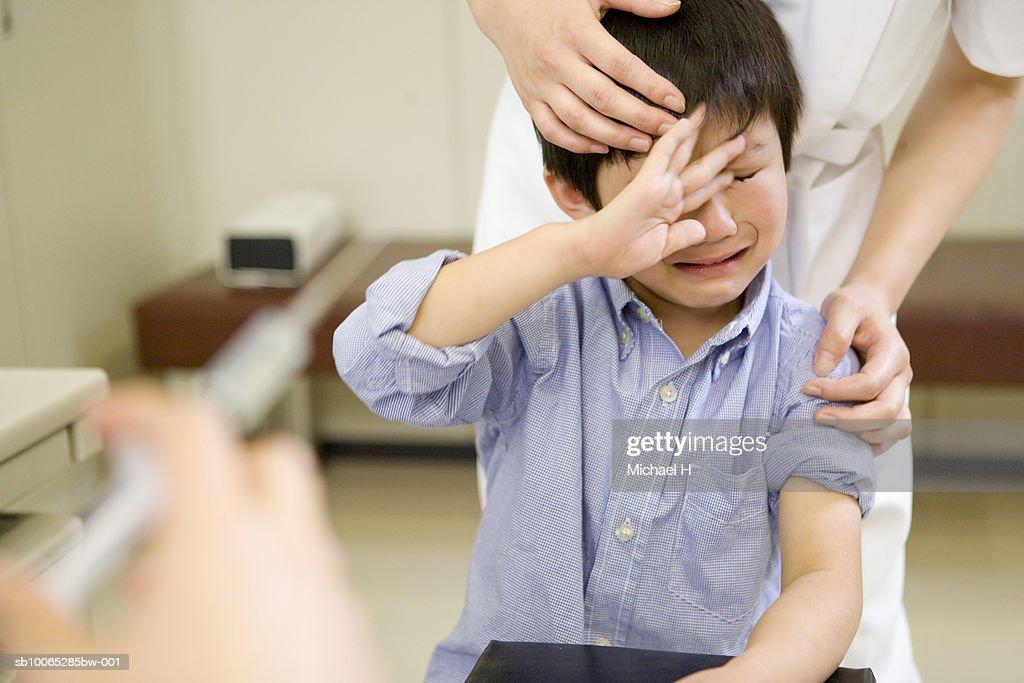 Boy (5-6) crying near syringe in hospital : Foto stock