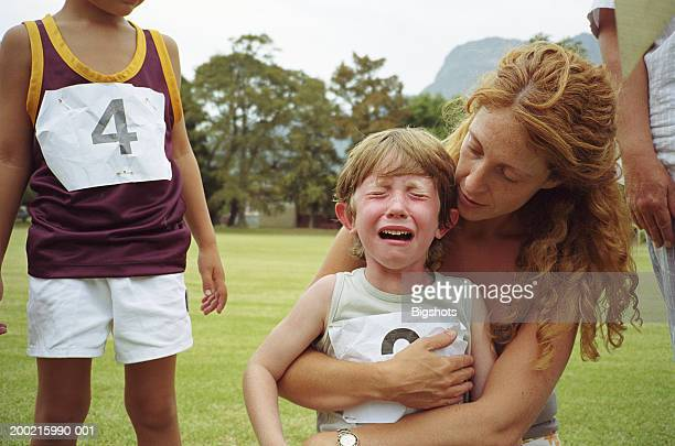 boy (4-6) crying while being comforted by mother at school sports day - derrota fotografías e imágenes de stock
