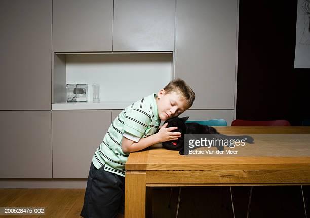 Boy (8-10) cuddling black cat on kitchen table, eyes closed