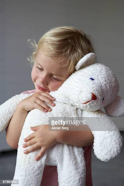 Boy cuddling toy bear