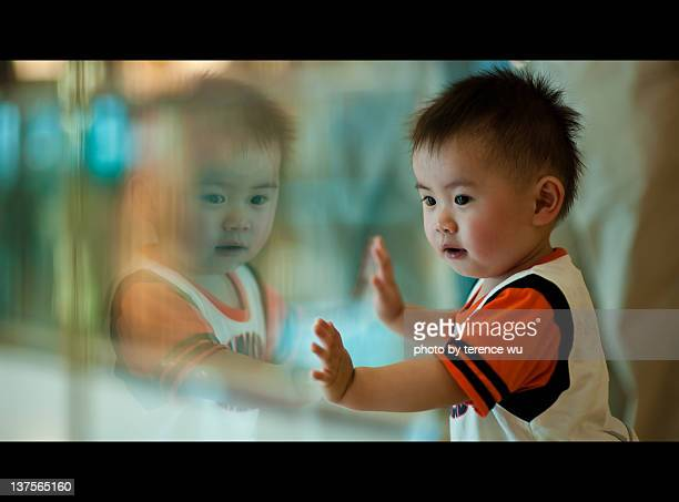Boy curiously looking at his own reflection