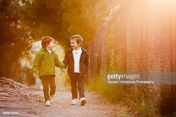 Boy cute boys, brothers, walking on pathway