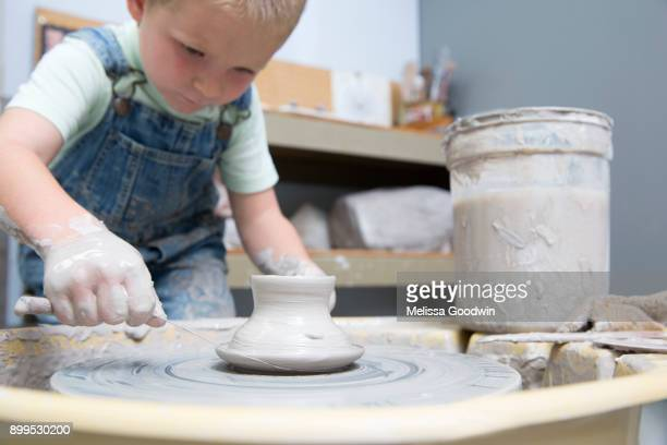 Boy cutting pot from potters wheel