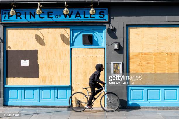 Boy cycles past the boarded up and shut Prince of Wales pub in Brixton, south London on April 23, 2020 as life in Britain continues under a lockdown...