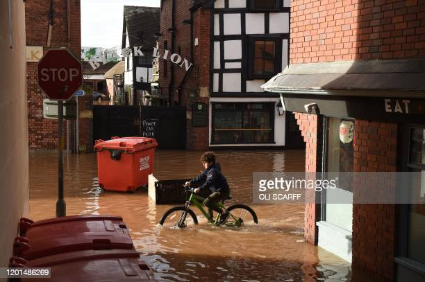 A boy cycles through flood water in Hereford western England on February 17 in the aftermath of Storm Dennis Britain on February 17 began to clear up...