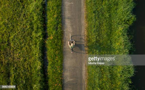 Boy cycling close to Mark river, Galder, Noord-Brabant, Netherlands