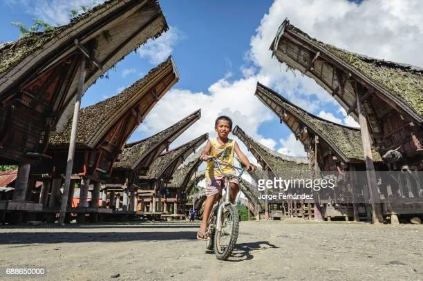 Boy cycling in a typical Tana Toraja village