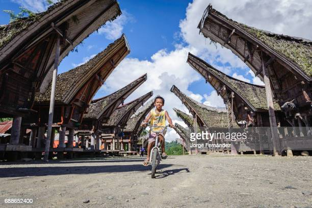 Boy cycling in a typical Tana Toraja village