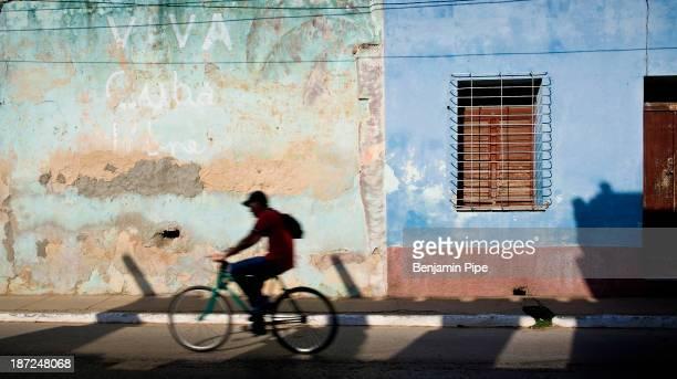 CONTENT] boy cycling past colourful walls Trinidad Cuba