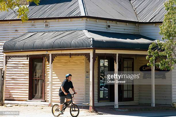 Boy cycling past old wooden house.
