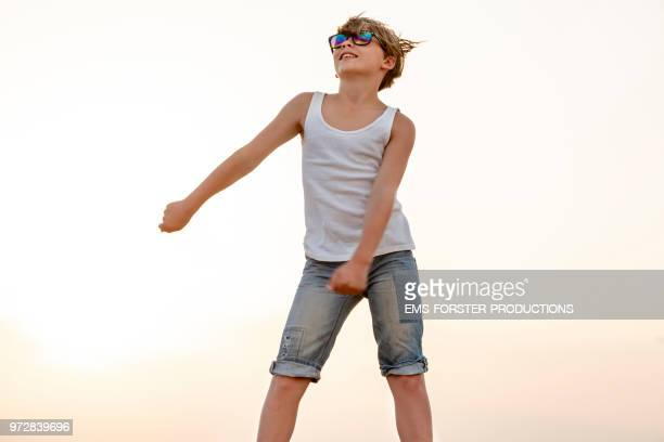 Boy dances the Fortnite floss move, aka swish shish dance, a on-trend dance inspired by the survival video game Fortnite.