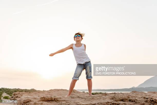 boy dances the fortnite floss move, aka swish shish dance, a on-trend dance inspired by the survival video game fortnite. - fortnite stock-fotos und bilder