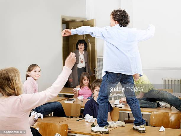 Boy (8-9) dancing in classroom and friends looking