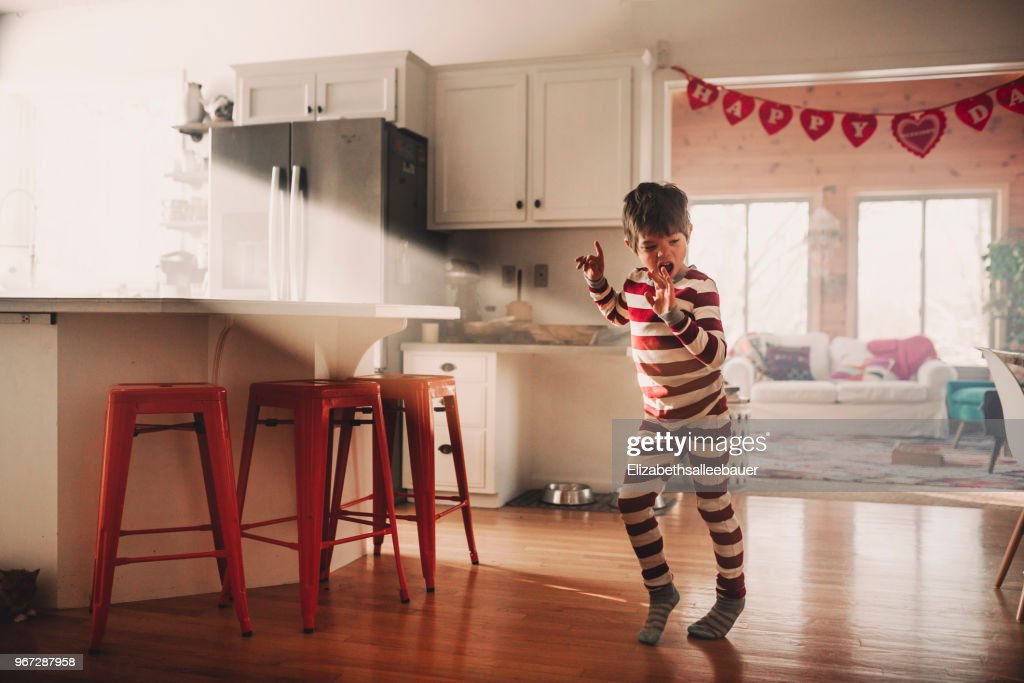 Boy dancing in the kitchen in his pyjamas : Stock Photo