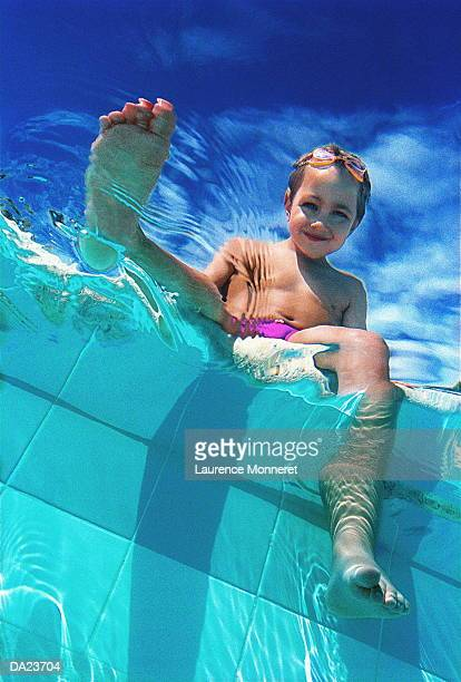 boy (8-10) dangling feet in swimming pool, low angle view - speedo boy stock photos and pictures