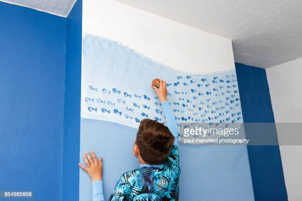 Boy decorating bedroom wall with potato print