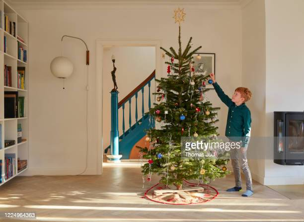 boy decorating christmas tree at home - christmas tree stock pictures, royalty-free photos & images