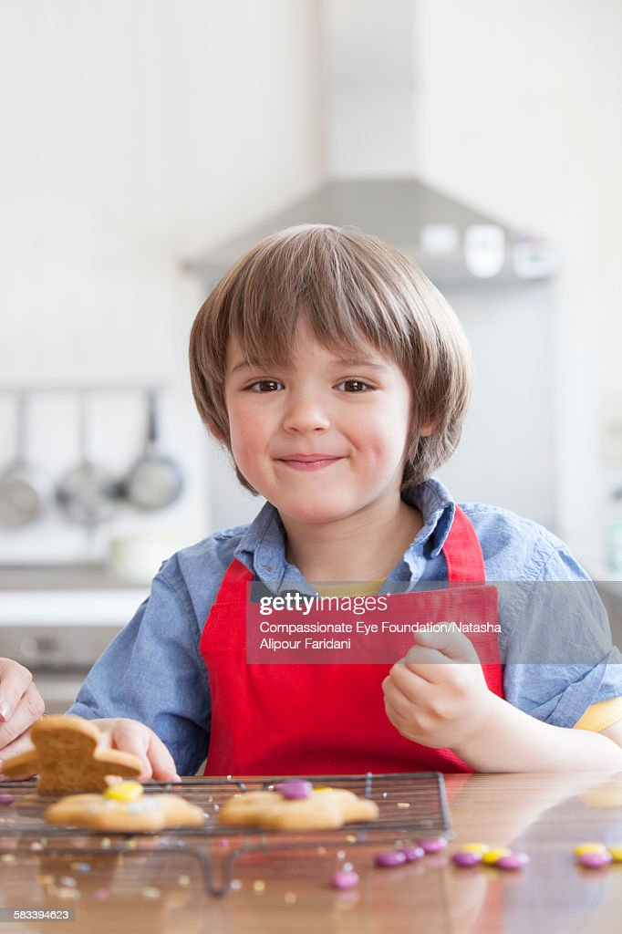 Boy decorating cookies in kitchen : Stock Photo