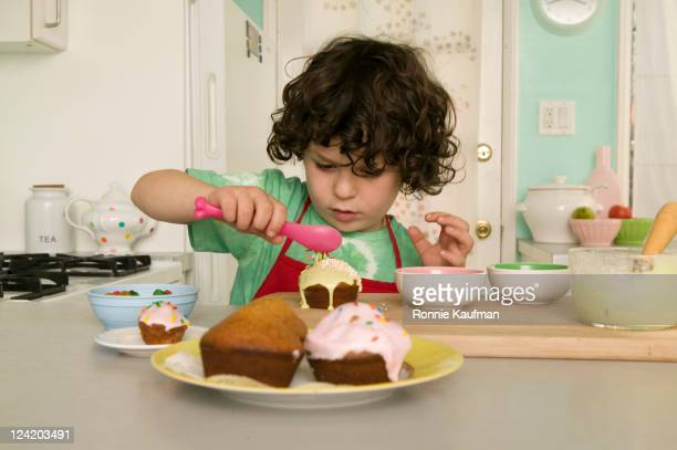 boy decorating cupcakes - decorating a cake stock pictures, royalty-free photos & images