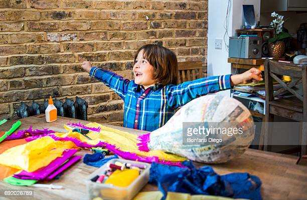 Boy decorating pinata at home