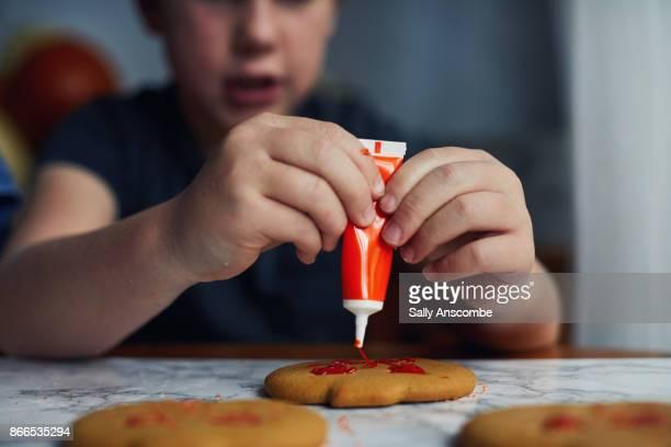 Boy decorating pumpkin shaped biscuits