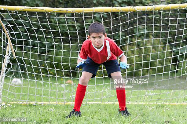 Boy (8-10) defending football goal