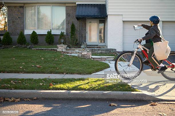 Boy delivering newspapers on his bicycle