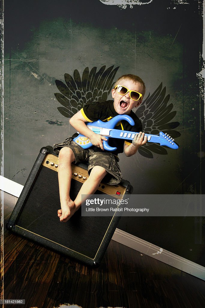 Boy demon sat on an amp with toy guitar : Bildbanksbilder
