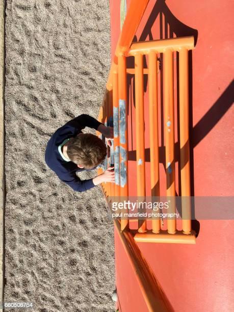 Boy descending down a ladder