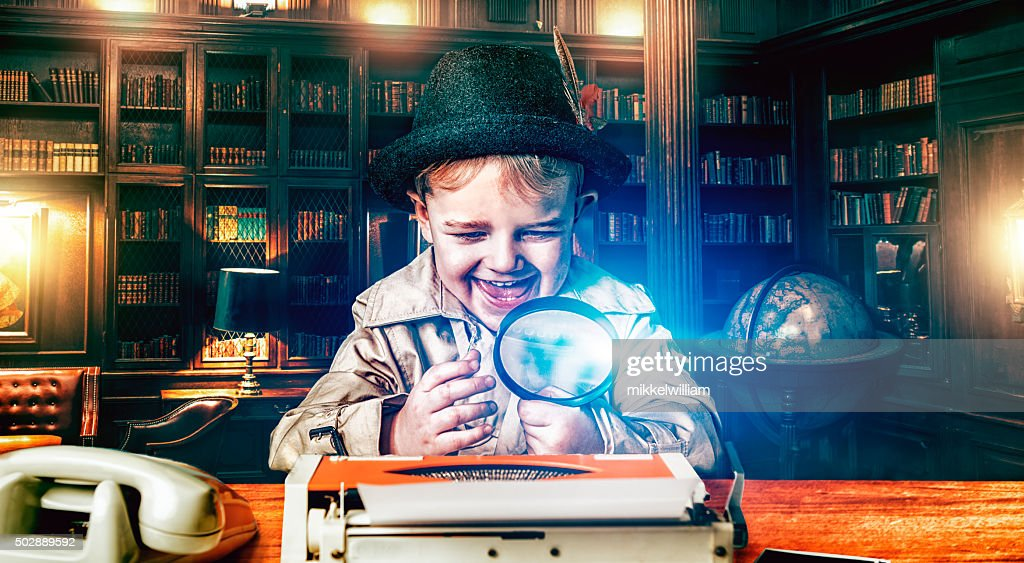 Boy detective with magnifying glass at work : Stock Photo