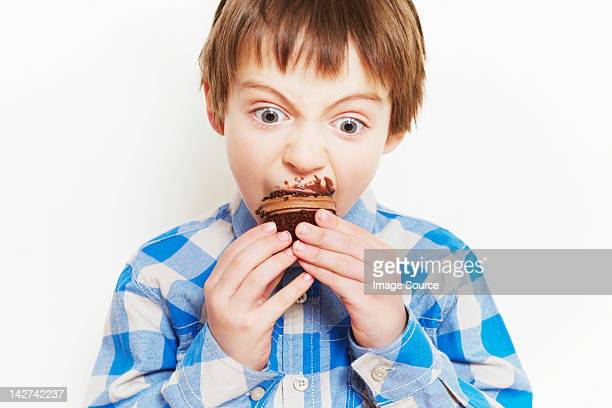 Boy devouring a cupcake
