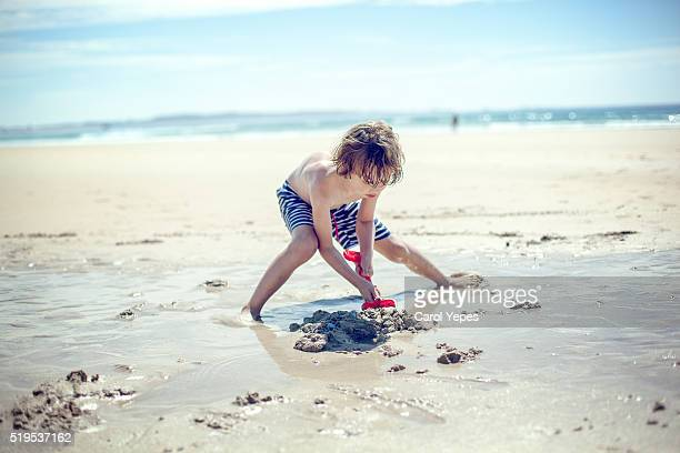Boy ( 8) digging a hole in the sand at beach